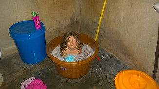 She bathes for awhile in the bucket and then I have to pour clean water to rinse off the African red dirt!